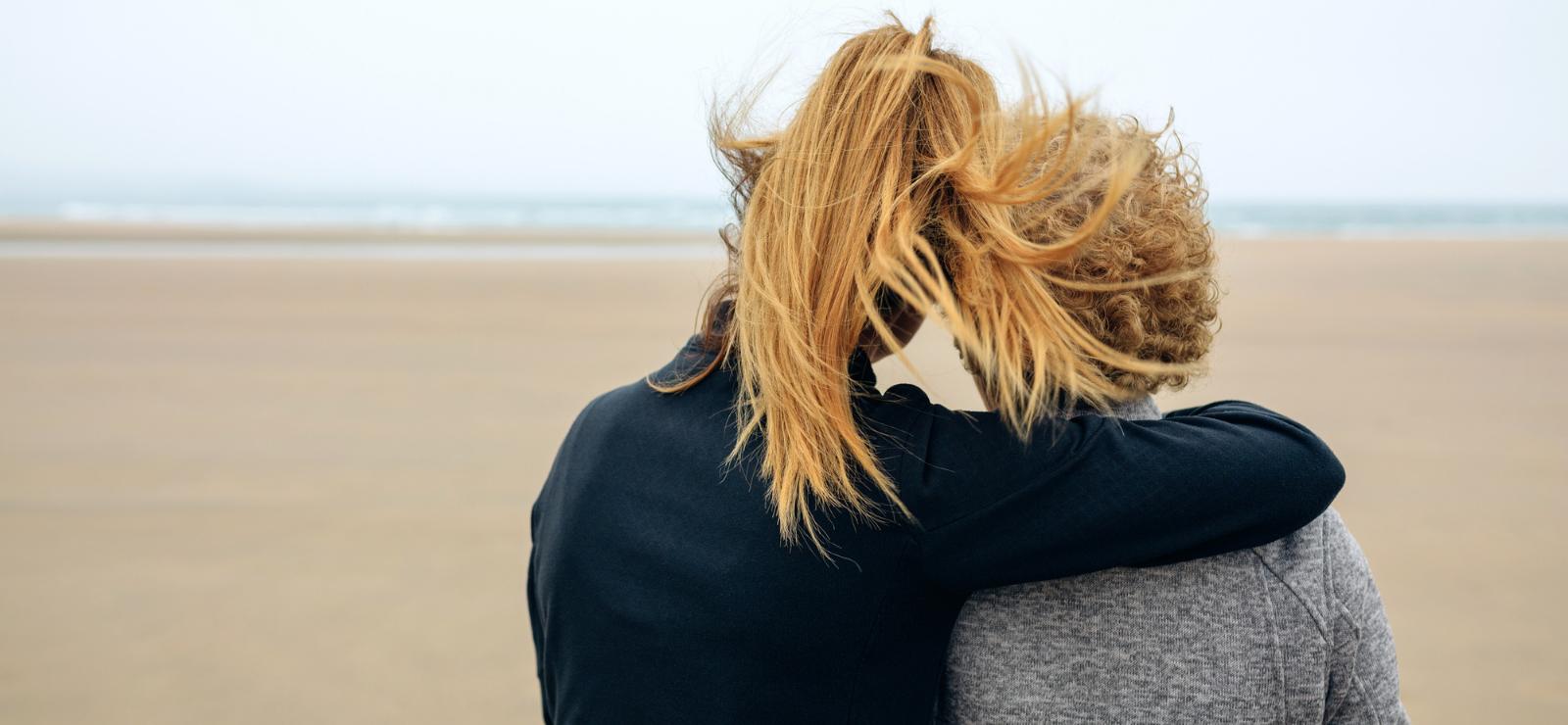 Kaksi naista katsoo merelle ja nojaa toisiinsa.