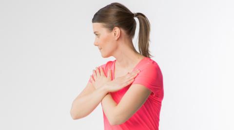 Nuori nainen kiertää rintarankaa kädet ristissä rinnan päällä.