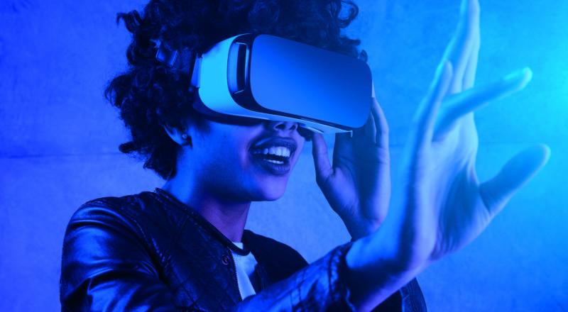Nuori nahkatakkinen tummaihoinen nainen kokeilee VR-silmikkoa ja tunnustelee kädellä ilmaa.