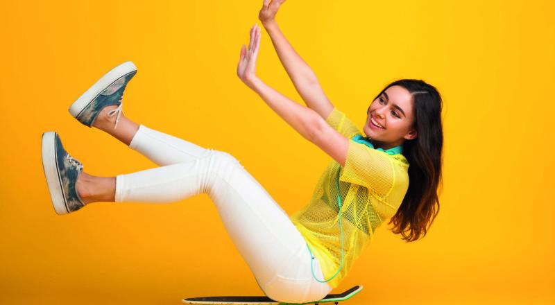 Nuori nainen istuu skeittilaudan päällä.