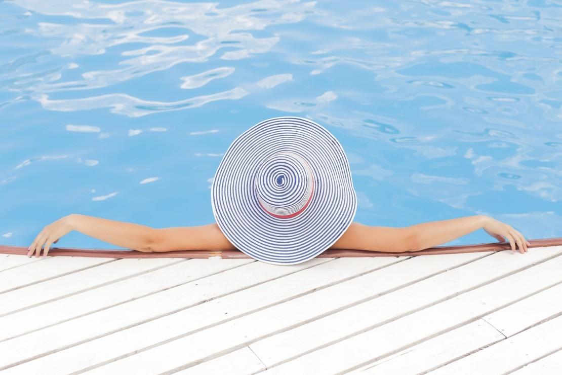 Nainen uima-altaassa lierihattu päässä.