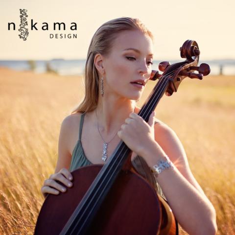 Naisella korvissa, kaulassa ja ranteessa Nikama-korut, pitää käsissään selloa, taustalla viljapelto.