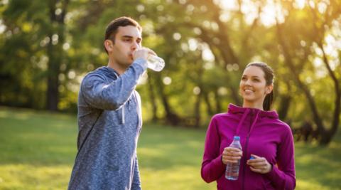 Pariskunta lenkillä puistossa, mies juo vettä pullosta.