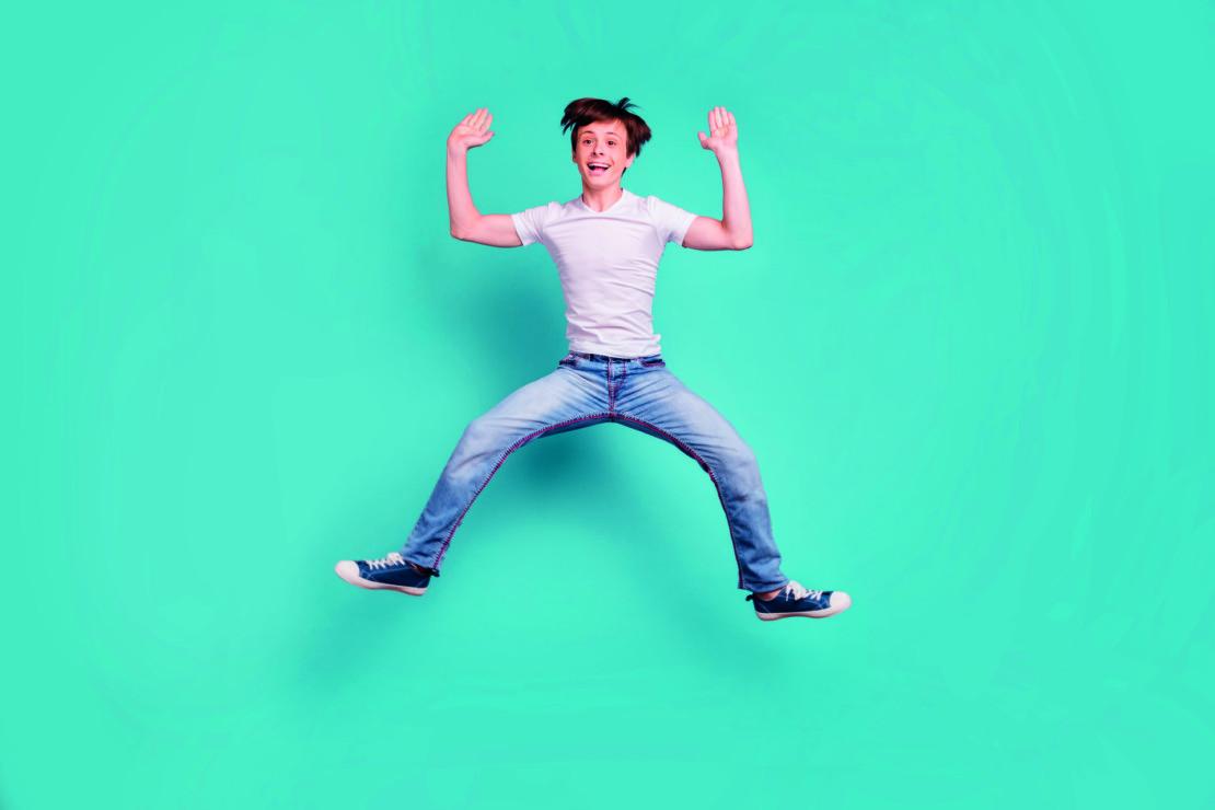 Nuori poika farkuissa ja valkoisessa t-paidassa hyppää ilmaan.