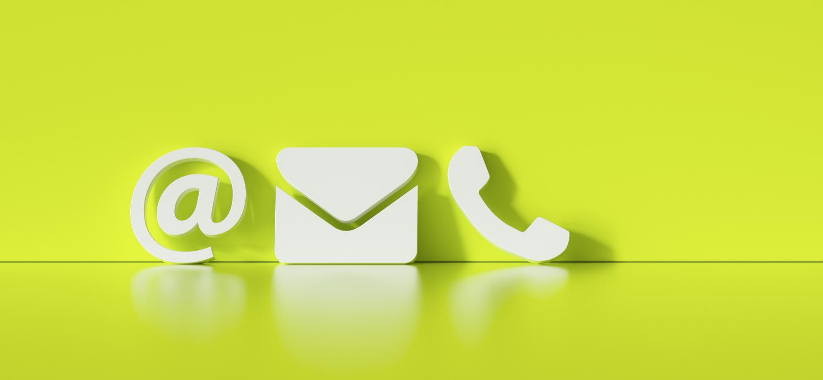 Yhteydenottosymbolit, sähköpostin @-merkki, kirjekuori ja puhelinluuri.